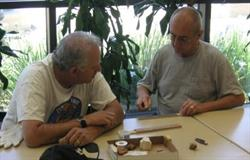 Two men sitting at table with art tools